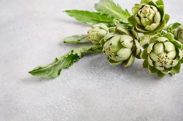 Verse organische artisjokken op een grijze concrete achtergrond. Premium Foto