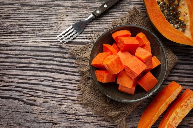 Verse papaja, in stukjes gesneden, op een zwarte plaat gelegd. Gratis Foto