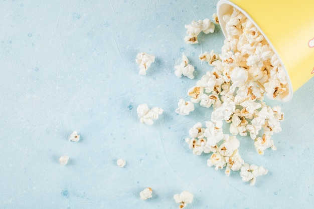 Verse popcorn verspreid over de blauwe tafel uit de doos Gratis Foto