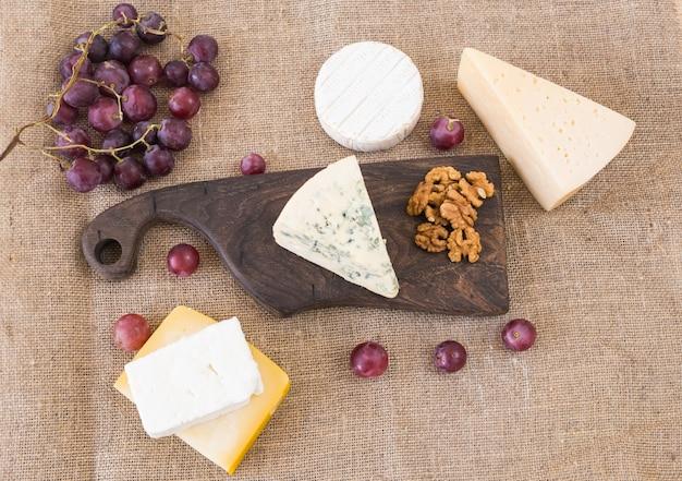 Verse producten. kaas, brie, camembert, druiven en noten op rustieke tafel. Premium Foto