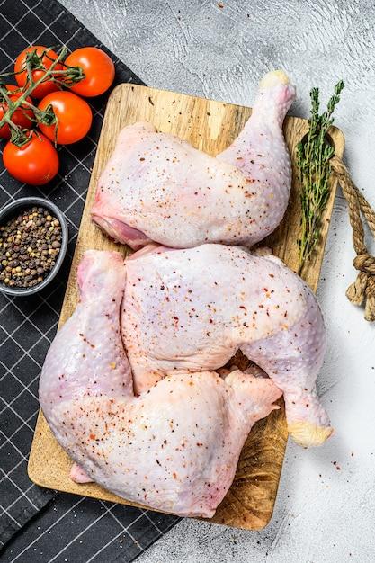 Verse rauwe kippendijen, benen op een snijplank met kruiden, koken. bovenaanzicht kopieer ruimte. Premium Foto