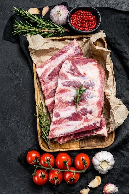 Verse rauwe varkensribbetjes met rozemarijn en knoflook in een houten kom. bovenaanzicht Premium Foto