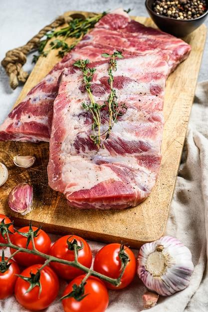 Verse rauwe varkensribbetjes met rozemarijn, peper en knoflook. Premium Foto