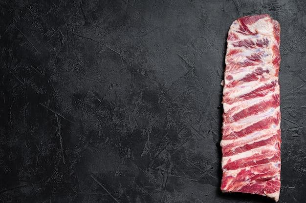 Verse rauwe varkensribbetjes. zwarte achtergrond. bovenaanzicht ruimte voor tekst Premium Foto