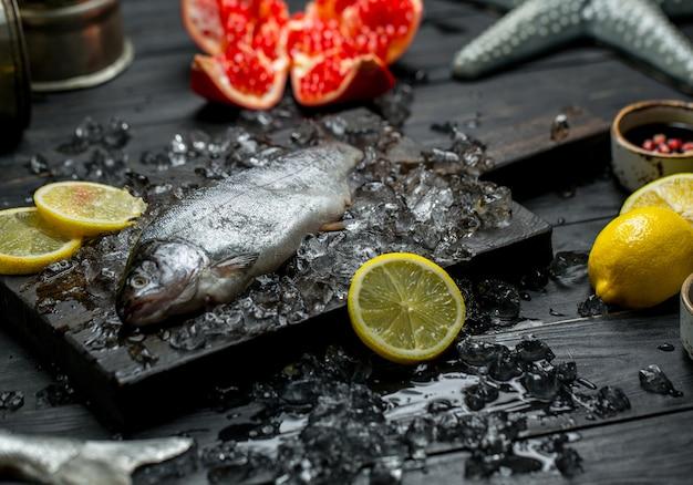 Verse rauwe vis, citroen, granaatappel en ijsblokjes. Gratis Foto