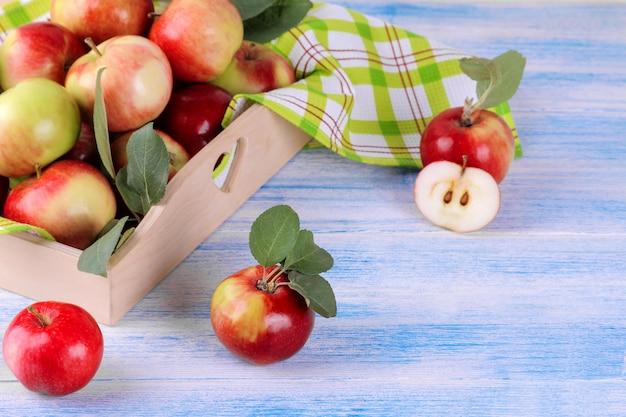 Verse rijpe appels in een houten bakje op een houten achtergrond Premium Foto