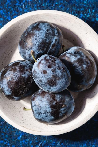 Verse rijpe pruimenvruchten in witte houten kom op blauwe abstracte achtergrond, hoogste mening Premium Foto