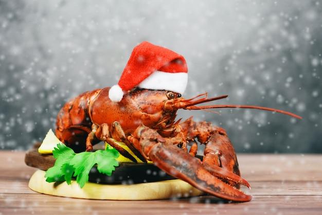 Verse rode zeekreeft met kerstmishoed bij kerstmislijst van het dinervoedsel het plaatsen Premium Foto