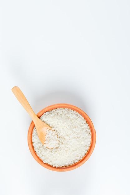 Verse ronde rijst in een houten kom met houten lepel hoogste mening over een witte achtergrond Gratis Foto