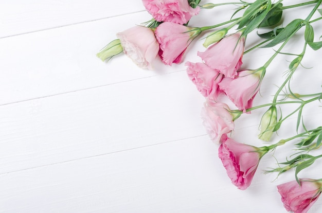 Verse roze eustoma bloemen op witte houten achtergrond Premium Foto