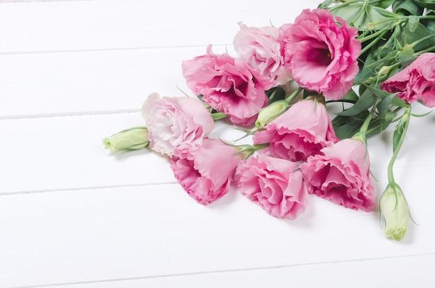 Verse roze eustomabloemen op witte houten Premium Foto