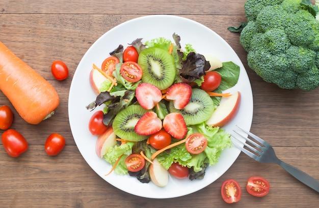 Verse salade met aardbeien, kiwi, tomaten en appels, bovenaanzicht Premium Foto