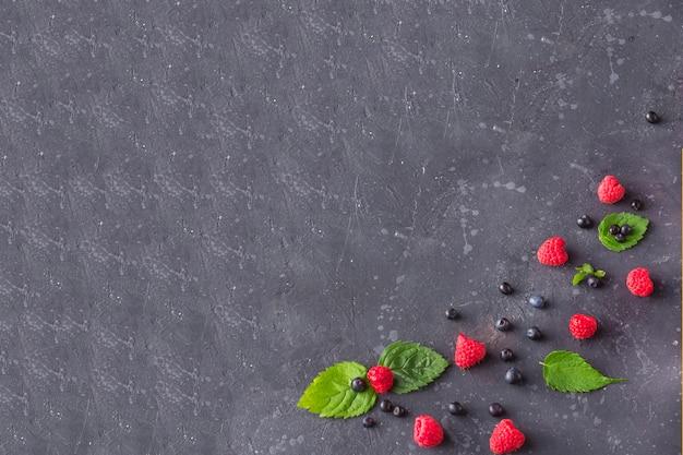 Verse sappige frambozen en bosbessen met muntblaadjes op een donkere achtergrond. zomerbessen op zwart. gezond, vegetarisch, eten, dieet. Premium Foto