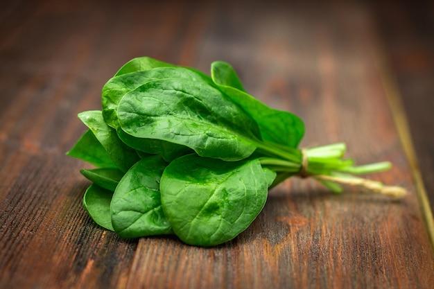 Verse, sappige spinazie bladeren op een houten bruin tafel. natuurlijke producten, groenten, gezonde voeding Premium Foto