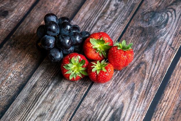 Verse schotse aardbeien en zwarte druiven bovenop houten lijst. Gratis Foto
