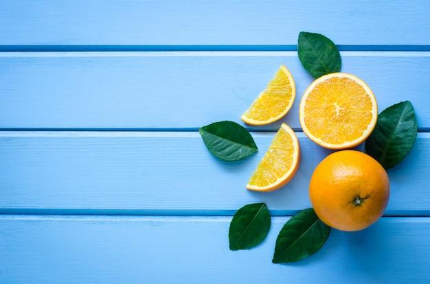 Verse sinaasappelen en sap op het blauwe hout Premium Foto