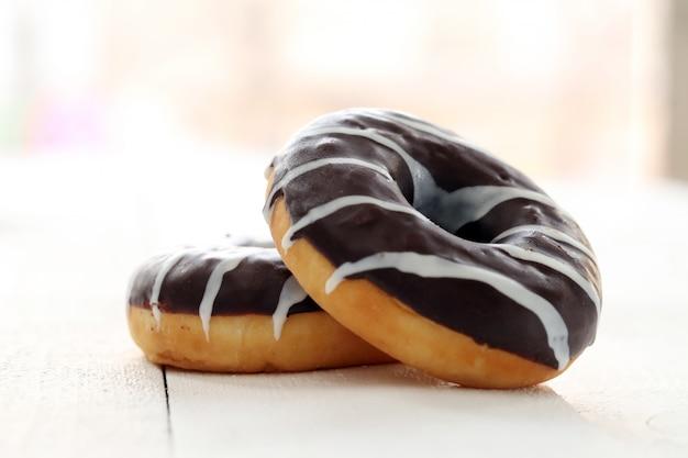 Verse smakelijke donuts met bruin glazuur Gratis Foto