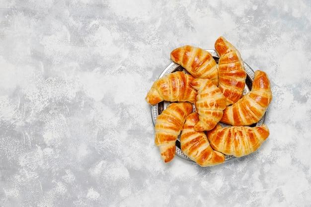Verse smakelijke eigengemaakte croissants op grijs-wit. frans gebak Gratis Foto