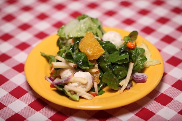 Verse smakelijke salade in een bord op een tafellaken Gratis Foto