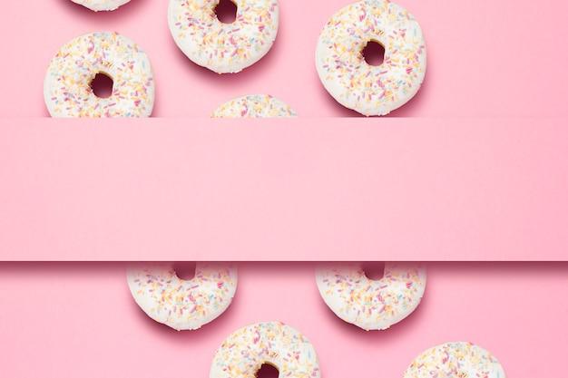 Verse smakelijke zoete donuts op een roze achtergrond. plaats voor tekst. concept van fast food, bakkerij, ontbijt, snoep. minimalisme. patroon. plat lag, bovenaanzicht, kopie ruimte. Premium Foto