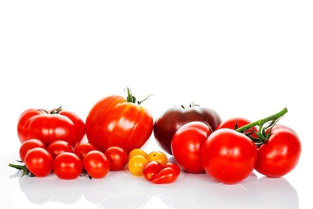 Verse tomaten met groene bladeren geïsoleerd op een witte achtergrond Premium Foto