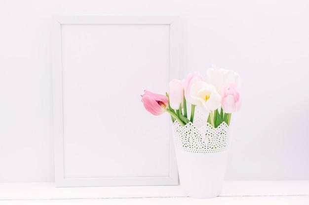 Verse tulpenbloemen in vaas met leeg fotokader Gratis Foto