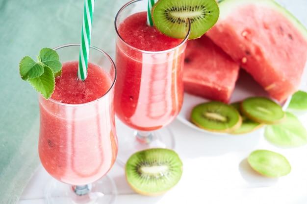 Verse watermeloen smoothie met kiwi en munt op een witte tafel Premium Foto