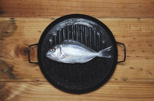 Verse wilde zeebrasem op grillpan klaar om te koken Gratis Foto