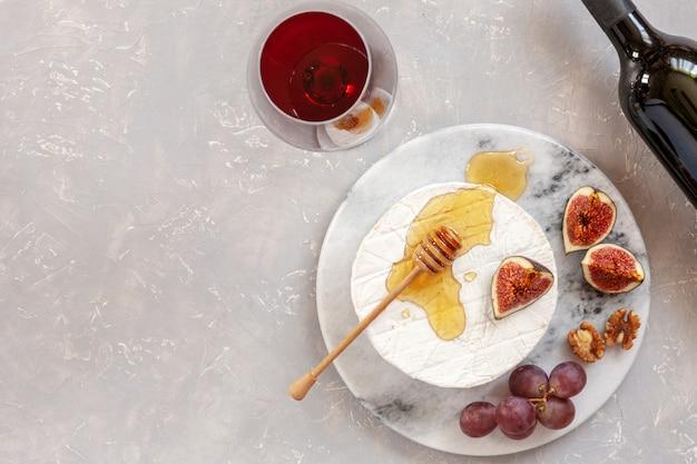 Verse zachte brie-kaas met honing, walnoten, vijgen, druiven en glas rode wijn. Premium Foto