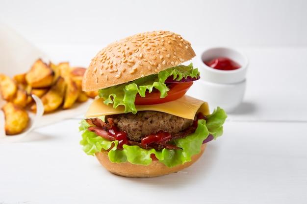 Verse zelfgemaakte hamburger met vlees, ketchup en frietjes op een lichte houten achtergrond. kopieer ruimte. Premium Foto
