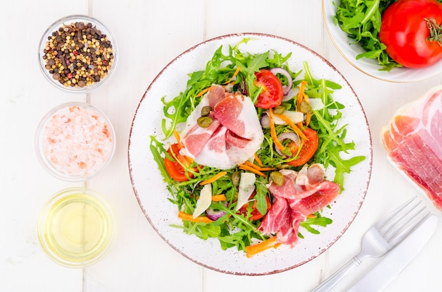 Verse zelfgemaakte salade met rucola, jamon, rucola, tomaten, parmezaanse kaas. Premium Foto