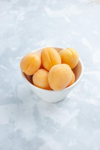 Verse zoete abrikozen zacht en lekker fruit in plaat op wit bureau, fruit vers zomer eten maaltijd vitamine Gratis Foto
