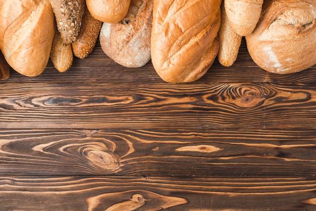 Versgebakken brood aan de bovenkant van houten achtergrond Gratis Foto