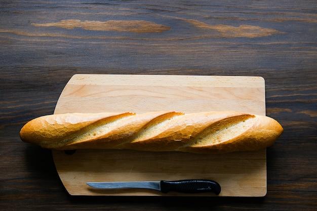 Versgebakken brood, een keukenmes met een zwart plastic handvat, een snijplank op een houten tafel. Premium Foto