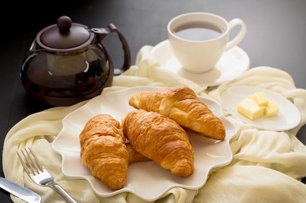 Versgebakken croissants en kopje thee op een witte plaat op een donkere tafel achtergrond. Premium Foto
