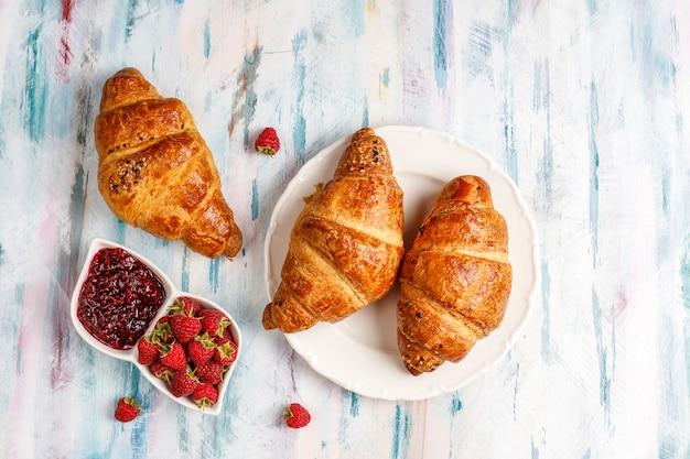 Versgebakken croissants met frambozenjam en frambozenfruit. Gratis Foto