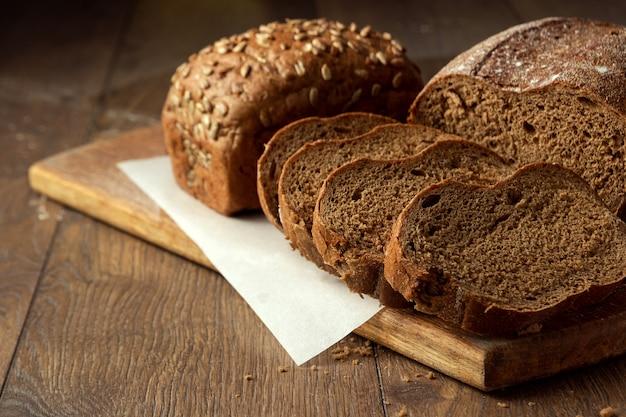 Versgebakken gesneden roggebrood op een houten snijplank Premium Foto