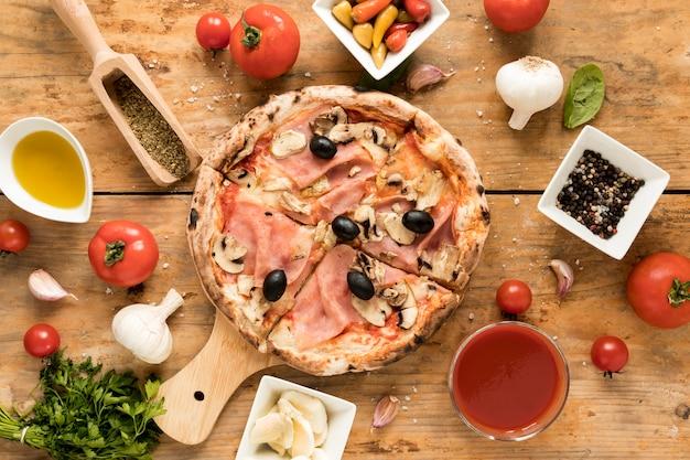 Versgebakken pizza omgeven met zijn ingrediënten op een getextureerd bureau Gratis Foto