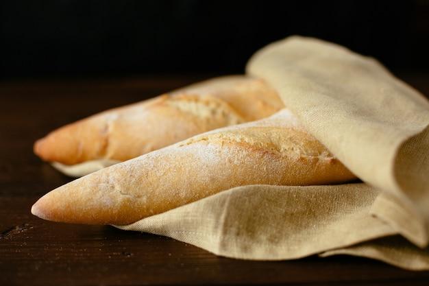 Versgebakken stokbrood. twee vers gebakken stokbrood gewikkeld in een bakkerij. Gratis Foto