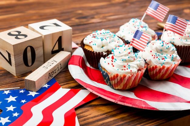 Versierde slagroom cupcakes met amerikaanse vlaggen op plaat en symbolen van onafhankelijkheid Gratis Foto