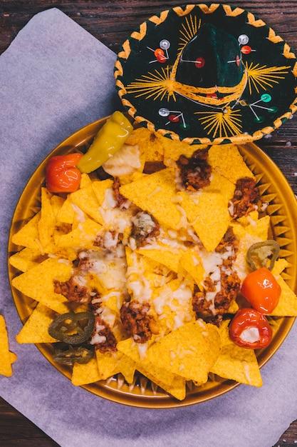 Versierde smakelijke mexicaanse nachos in plaat met mexicaanse hoed op tafel Gratis Foto
