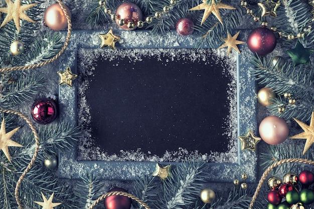 Versierde spartakjes rond schoolbord op rustiek hout met sneeuw. bovenaanzicht met kopie ruimte. Premium Foto