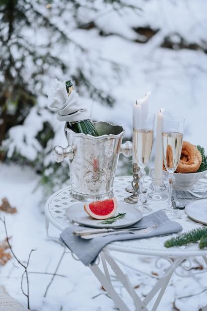 Versierde tafel voor een romantisch diner met kaarsen, mousserende wijn en fruit in het winterbos Premium Foto