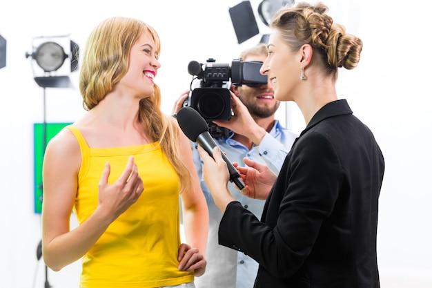Verslaggever en cameraman schieten een interview Premium Foto