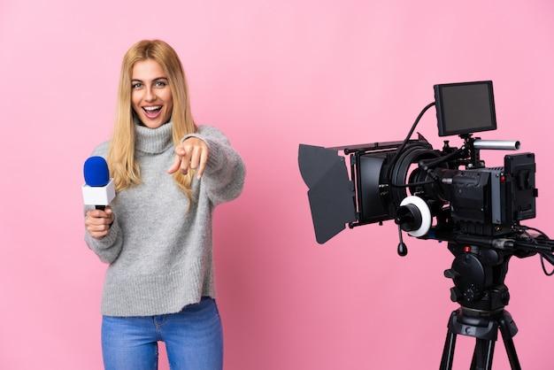 Verslaggeversvrouw die een microfoon houden en nieuws over geïsoleerd roze richten die voorzijde met gelukkige uitdrukking richten Premium Foto