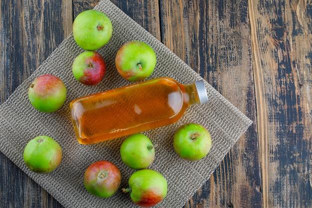 Verspreide appels met drankje plat lag op houten en placemat achtergrond Gratis Foto