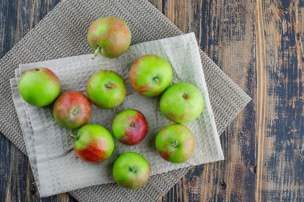 Verspreide appels met keukenpapier op houten en placemat achtergrond, plat leggen. Gratis Foto