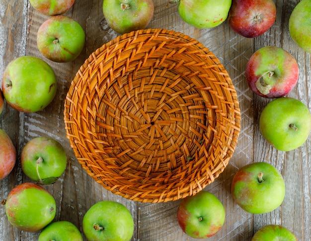 Verspreide appels met lege mand op hout Gratis Foto
