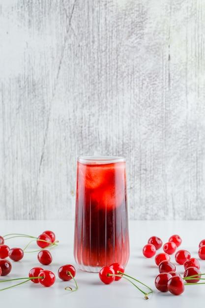 Verspreide kersen met ijzig drankje zijaanzicht op witte en grungy tafel Gratis Foto