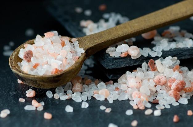 Verspreide roze himalayan-zout en houten lepel, gezondheid, wellnessconcept. Premium Foto